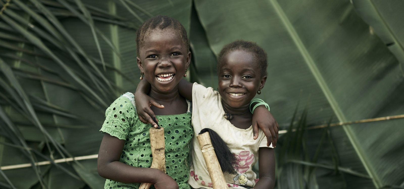 Portrait of two young girls from the village of Tombohuan hugging and smiling
