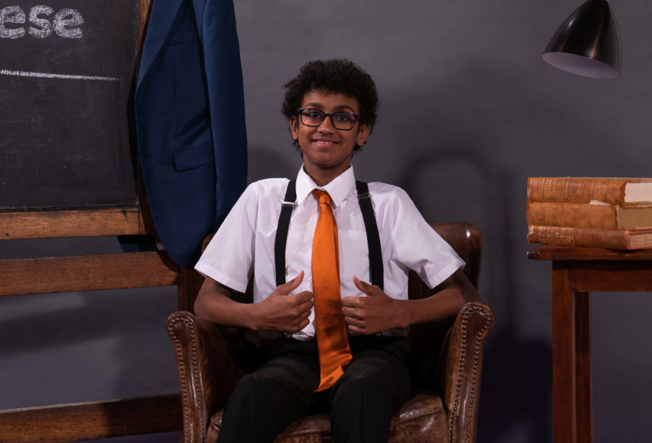 Tyrese, a young boy, waiting in a chair to teach sign language