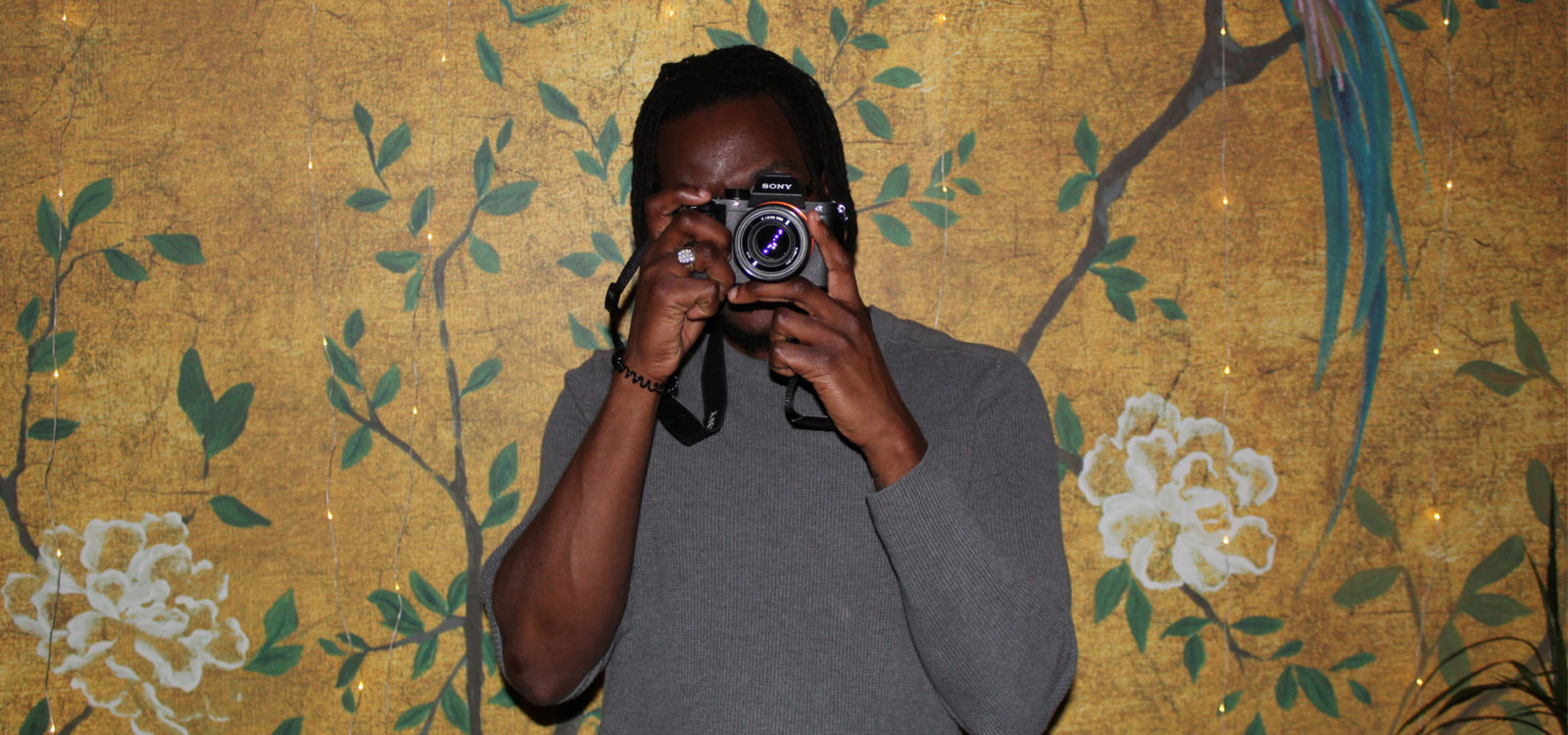 Male holding camera taking photo head on