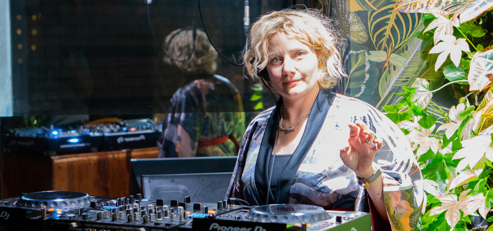 Lady with short blonde hair as DJ