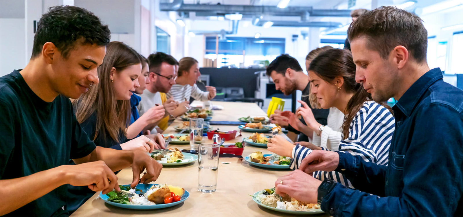 Various agency colleagues eating lunch together on long table